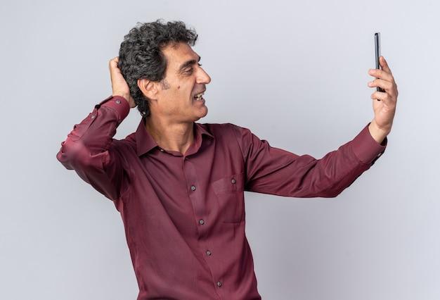 스마트 폰을 사용하여 셀카를하고 보라색 셔츠에 수석 남자가 행복하고 긍정적으로 웃고