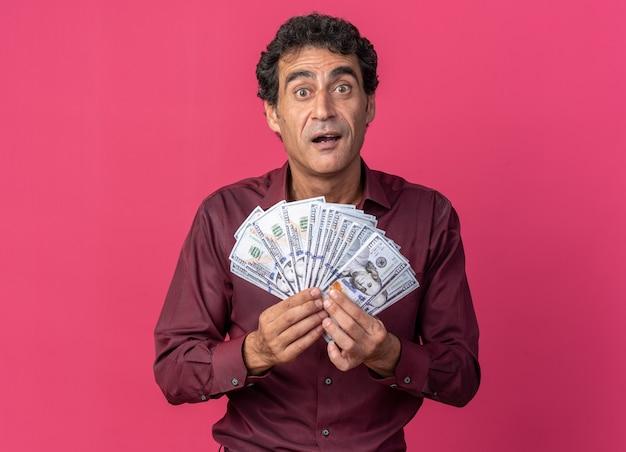 분홍색 배경 위에 서서 행복하고 흥분된 카메라를 바라보는 현금을 들고 보라색 셔츠를 입은 노인