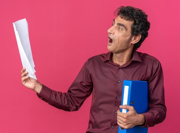 폴더와 빈 페이지를 들고 있는 보라색 셔츠를 입은 수석 남자는 분홍색 배경 위에 서서 놀라고 놀랐습니다.