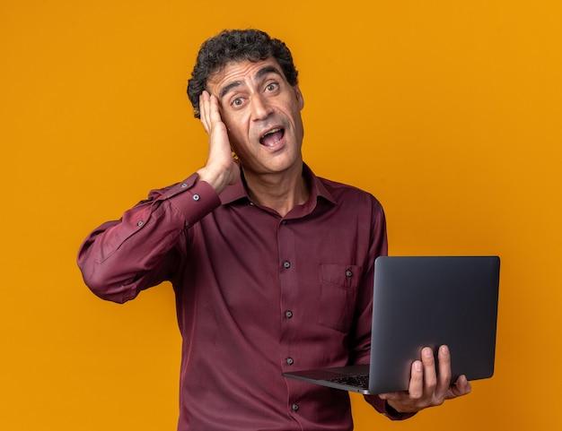 カメラを見ているラップトップを保持している紫色のシャツを着た年配の男性は、オレンジ色の背景の上に立っている彼の頭の上の手で混乱し、驚いた