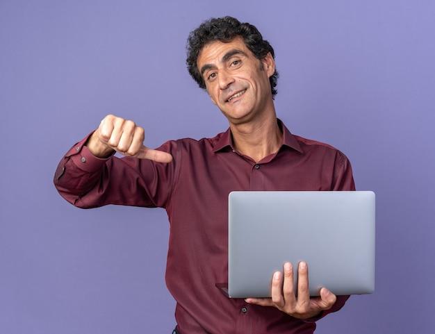 青い背景の上に立っている自分を指して自信を持って笑顔のカメラを見てラップトップを保持している紫色のシャツの年配の男性