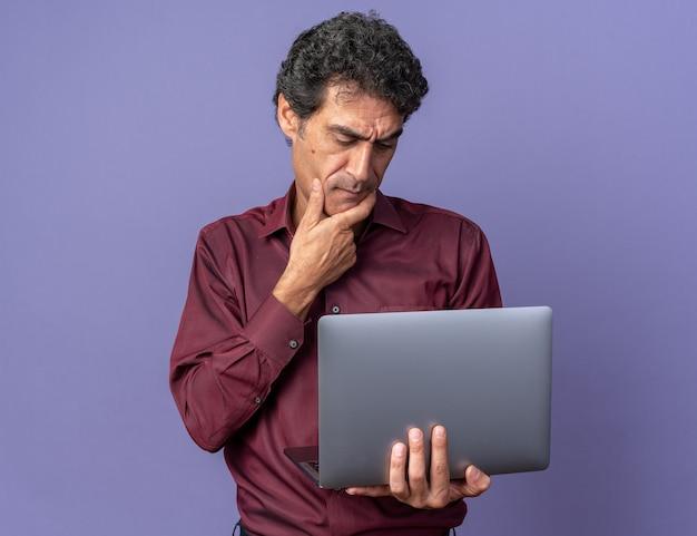 困惑した画面を見ているラップトップを保持している紫色のシャツの年配の男性