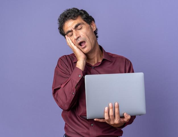 Старший мужчина в фиолетовой рубашке держит ноутбук, выглядит усталым и скучающим, зевая