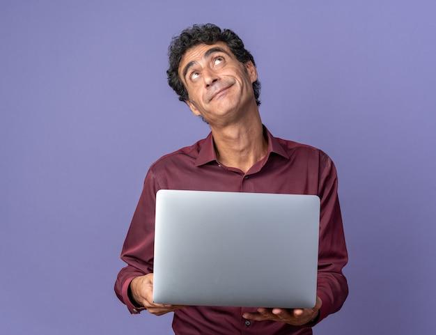 얼굴에 회의적인 미소로 올려 노트북을 들고 보라색 셔츠에 수석 남자