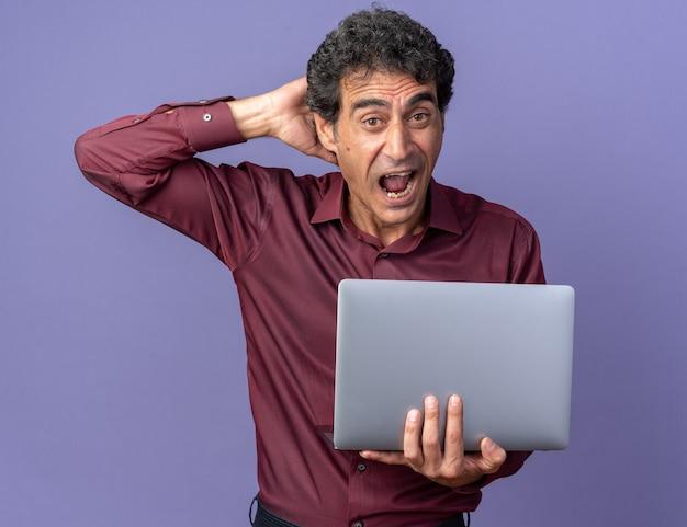青い背景の上に立って驚いて驚いたように見えるラップトップの叫びを保持している紫色のシャツを着た年配の男性