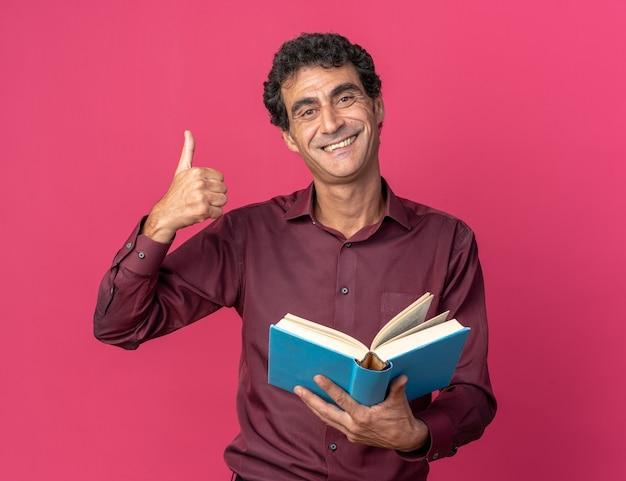 ピンクの背景の上に立って元気に親指を見せて笑顔のカメラを見て開いた本を保持している紫色のシャツの年配の男性