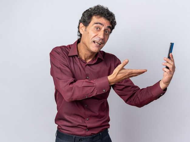 幸せで前向きな手の腕でi番目を提示するスマートフォンを保持している紫色のシャツの年配の男性