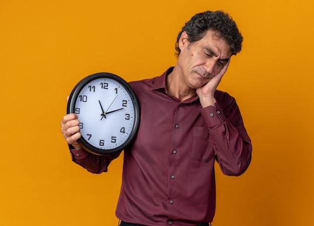 Старший мужчина в фиолетовой рубашке, держащий настенные часы, выглядит усталым и скучающим