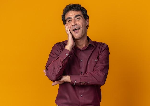 Старший мужчина в фиолетовой рубашке смотрит в камеру счастливым и веселым улыбающимся стоя на оранжевом фоне