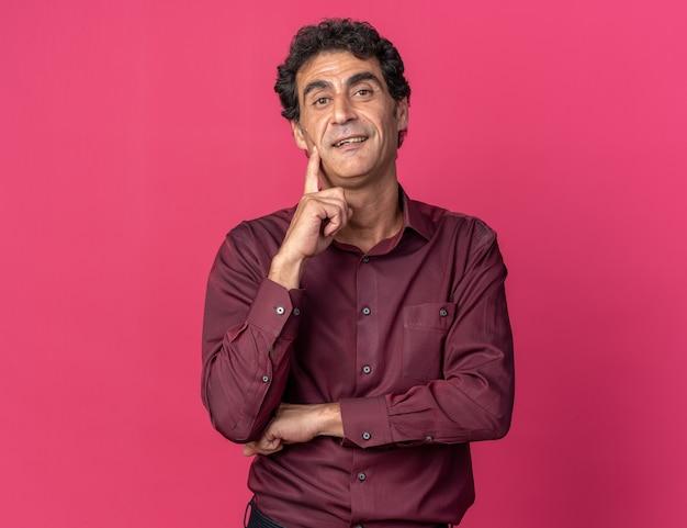 ピンクの上に立っている彼の頬に指で幸せで自信を持って笑顔でカメラを見て紫色のシャツを着た年配の男性