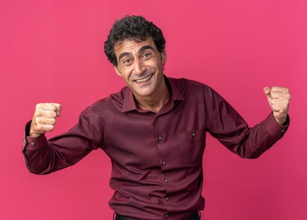 보라색 셔츠를 입은 노인이 분홍색 배경 위에 서서 행복하고 흥분된 주먹을 꽉 쥐고 카메라를 바라보고 있습니다.