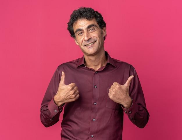ピンクの上に立って親指を元気に見せて幸せで前向きな笑顔のカメラを見て紫色のシャツを着た年配の男性