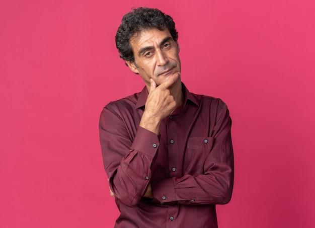 분홍색 배경 위에 서 있는 어리둥절한 카메라를 보고 있는 보라색 셔츠를 입은 노인