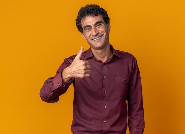 카메라를보고 보라색 셔츠에 수석 남자 자신감 보여주는 엄지 손가락 미소