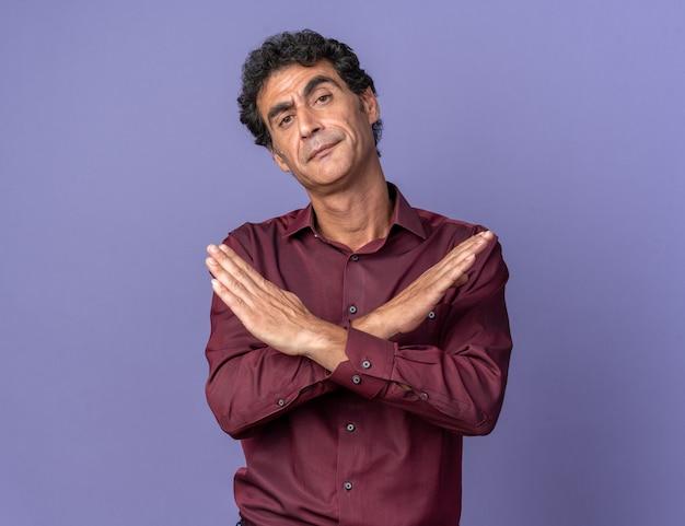 紫のシャツを着た年配の男性が真面目な顔でカメラを見て、青の上に立っている手を交差させるジェスチャーを停止します