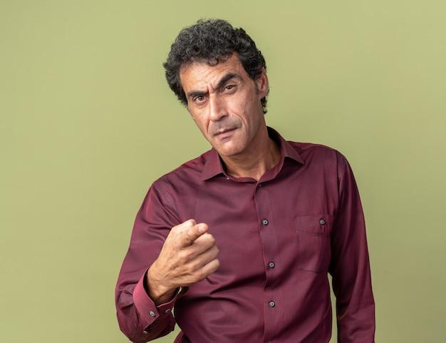 カメラに人差し指で指している懐疑的な表情でカメラを見ている紫色のシャツの年配の男性