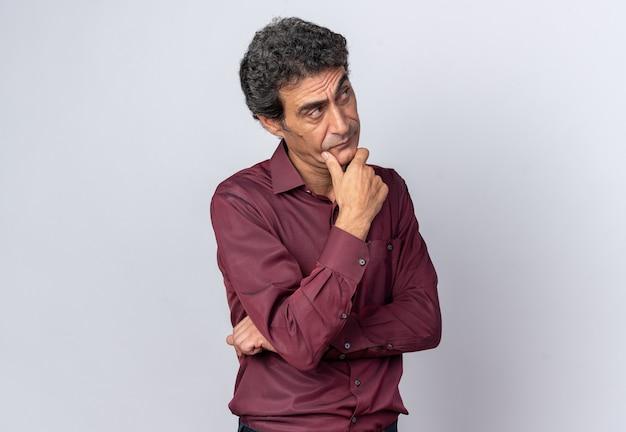 Старший мужчина в фиолетовой рубашке смотрит вверх озадаченно думая, стоя на белом фоне