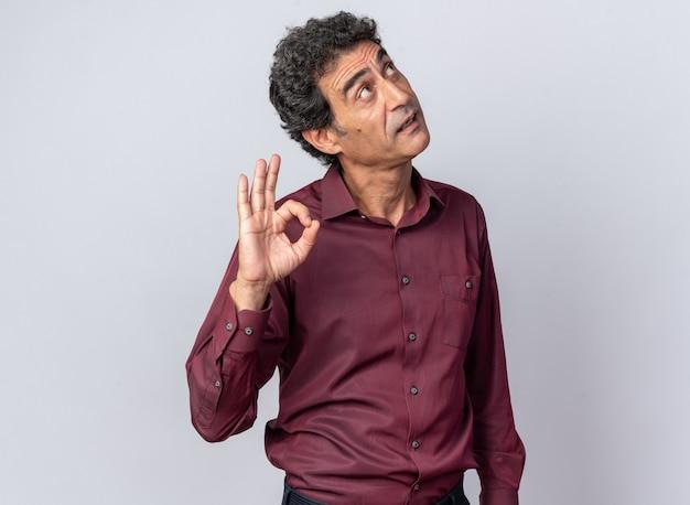 白の上に立ってokサインをやって笑って見上げる紫色のシャツの年配の男性