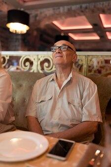 레스토랑에서 뭔가를 흥미롭게 보고 있는 시니어 남자