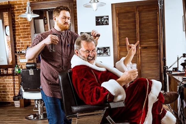 Старший мужчина в костюме санта-клауса бреет своего личного мастера в парикмахерской перед рождеством