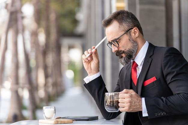 Старший мужчина в умном деловом костюме думает и сидит за журнальным столиком на открытом воздухе.