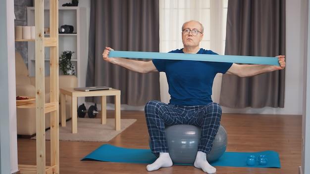 レジスタンスバンドで運動するスポーツウェアの年配の男性。老人年金受給者が自宅でヘルスケアスポーツを健康的に訓練し、高齢者でフィットネス活動を行う