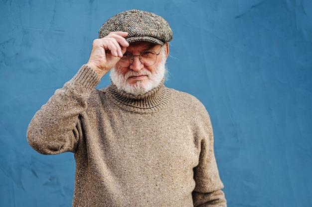 Старший мужчина в свитере и кепке. пожилой бородатый мужчина в вязаном свитере и очках