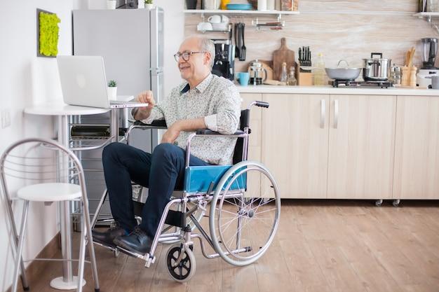 キッチンでラップトップを使用して車椅子の年配の男性。キッチンのラップトップでビデオ会議をしている車椅子の障害者の年配の男性。オンライン会議をしている麻痺した老人と彼の妻。