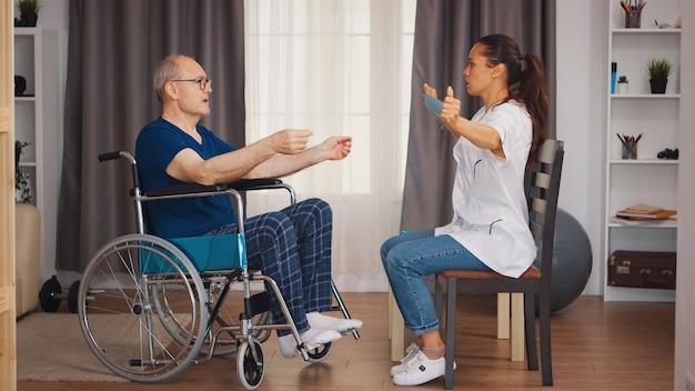 医師の助けを借りてリハビリテーション中に抵抗バンドを使用して車椅子の年配の男性。回復支援療法理学療法ヘルスケアシステムのソーシャルワーカーと障害者障害者老人