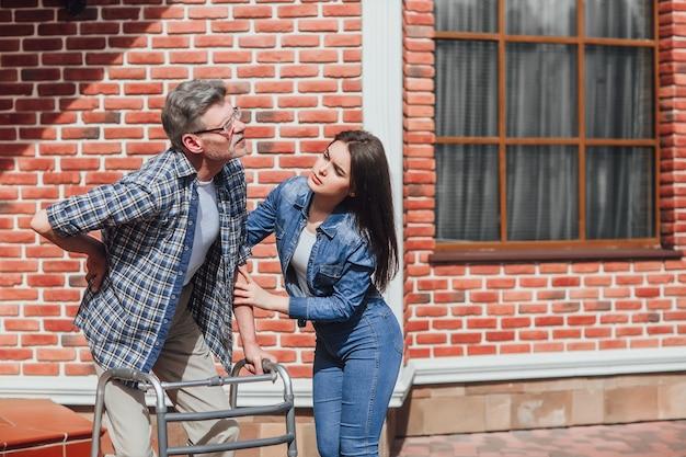 Старший мужчина в инвалидной коляске с дочерью возле больницы