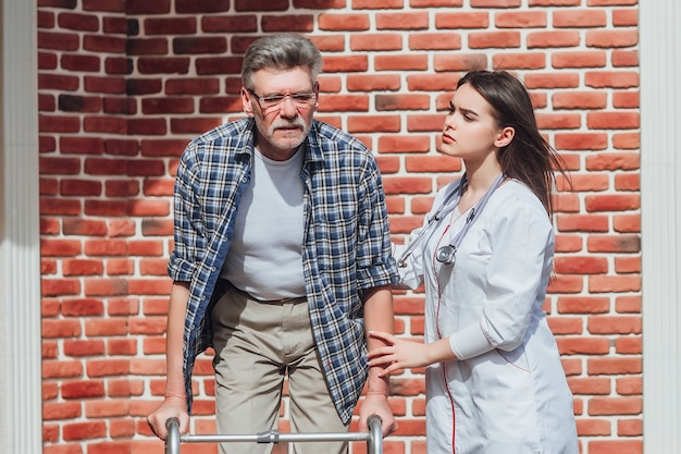 病院の庭を散歩している看護師と車椅子の年配の男性