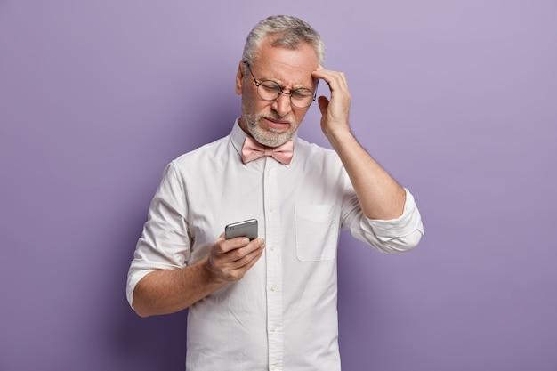 Старший мужчина в белой рубашке и розовом галстуке-бабочке держит телефон
