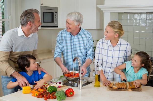 Старший мужчина, общение с семьей во время приготовления пищи на кухне