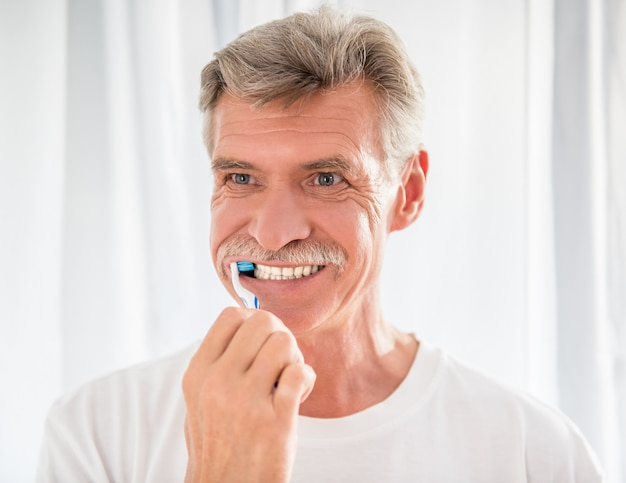 Старший мужчина чистит зубы и улыбается.