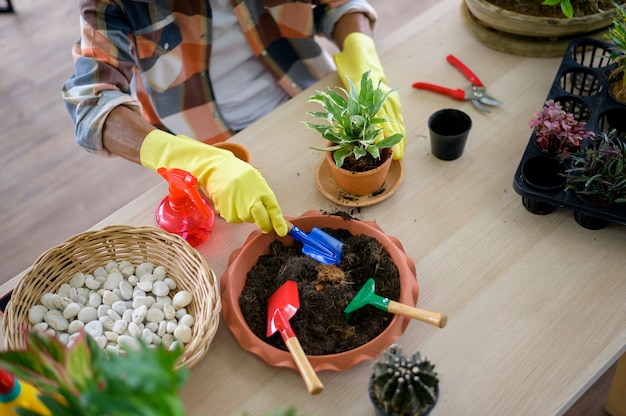 Старший мужчина сажает садовые инструменты на деревянный пол, концепция хобби и отдыха