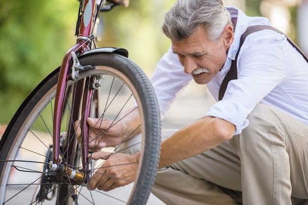Senior man is repairing bike in the street.