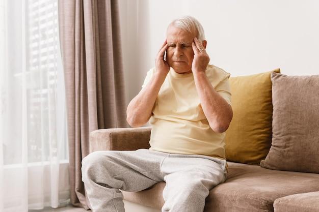年配の男性は家で頭痛に苦しんでいます