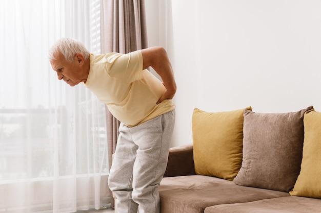年配の男性が腰の痛みに苦しんでいます