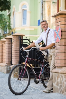 年配の男性は通りで自転車で歩いています。