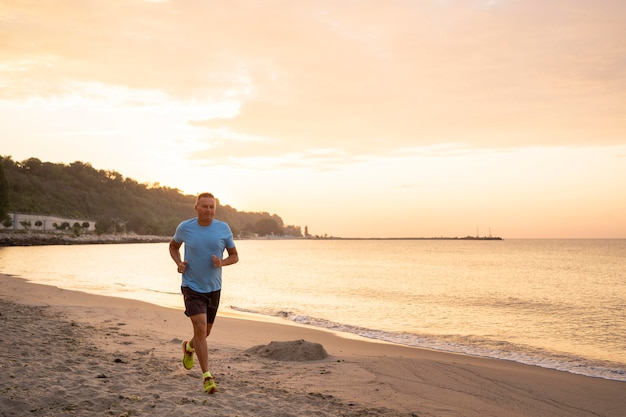 Senior man jogging on the beach with copy space