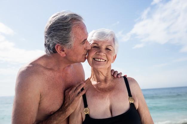 Старший мужчина целует старшую женщину в щеку