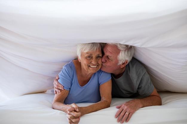 Старший мужчина целует женщину под одеялом на кровати в спальне