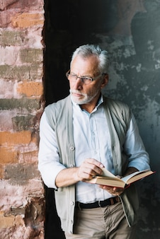 Senior man leaning on brick wall holding book