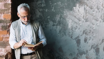 Senior man leaning to brick wall reading book