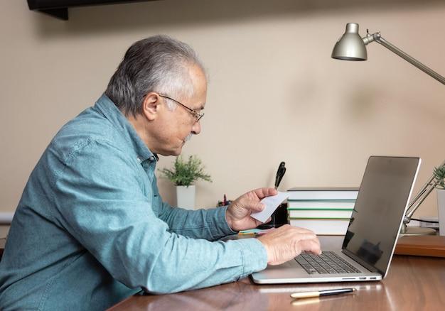 수석 남자는 컴퓨터를 사용하는 방법을 배웁니다. 유리와 파란색 셔츠를 입은 노인 종이에서 암호를 입력합니다. 홈 오피스에서 온라인 공부를 위해 랩톱 컴퓨터를 사용하는 개념