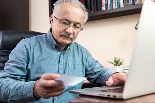 수석 남자는 컴퓨터를 사용하는 방법을 배웁니다. 집에서 사무실에서 온라인 공부를 위해 랩톱 컴퓨터를 사용하는 유리와 파란색 셔츠에 노인