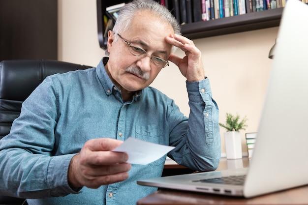 年配の男性はコンピューターの使い方を学びます。ホームオフィスでオンライン学習のためのラップトップコンピューターを使用してガラスと青いシャツの老人