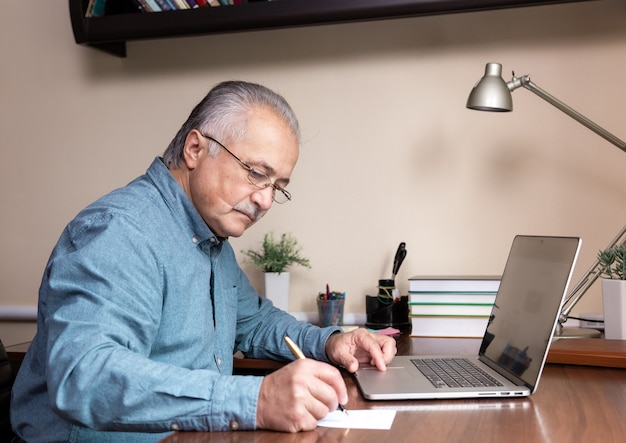 Senior man learn to use computer. old man in glass and blue shirt using a laptop computer for online studying at home office