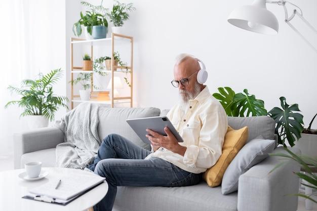 Старший мужчина учится с планшетом