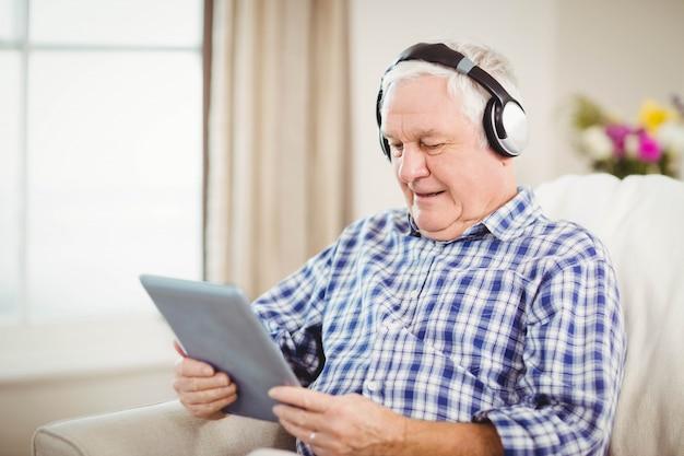 Senior man listening to music on digital tablet